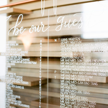 wedding seating chart white lettering on glass