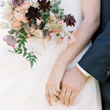 couple holds hands featuring simple vintage inspired wedding rings