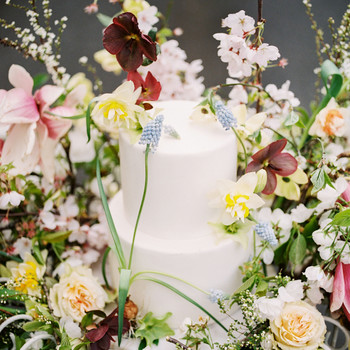 two tiered white frosted wedding cake surrounded by floral display