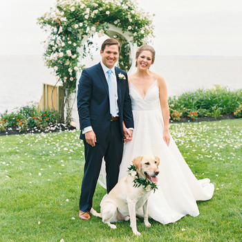 bride and groom standing outside next to floral arch with their yellow lab dog