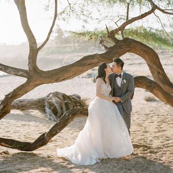 bride and groom hawaiian wedding kiss by beach tree