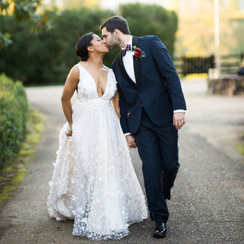 bride and groom share a kiss while holding hands