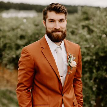 groom in burnt orange wedding suit outside