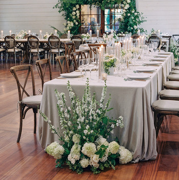 long reception table with neutral cloth and white and green decor