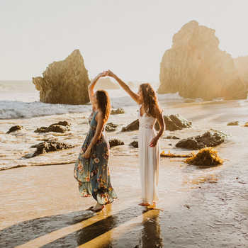 couple twirling on beach engagement photo