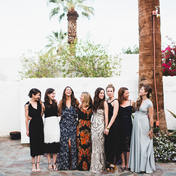 group of women in wedding guests dresses pose for photo