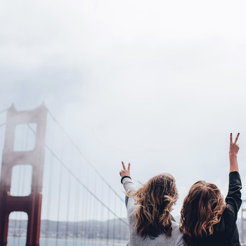 san francisco women standing in front of golden gate bridge foggy day