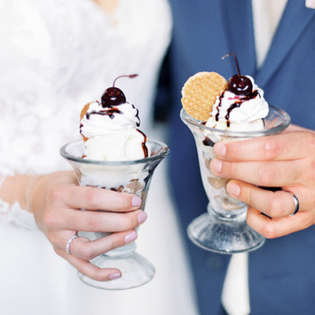 bride and groom each holding an ice cream sundae