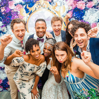 wedding guests pose with bride groom photobooth