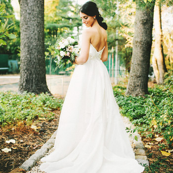 woman standing in garden in wedding dress- classic hair and makeup