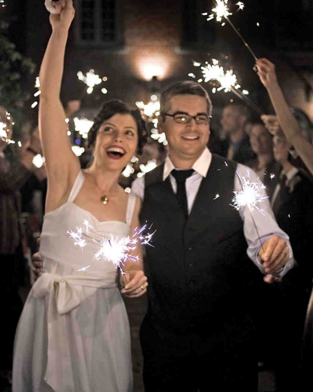 bride and groom holding purple sparklers