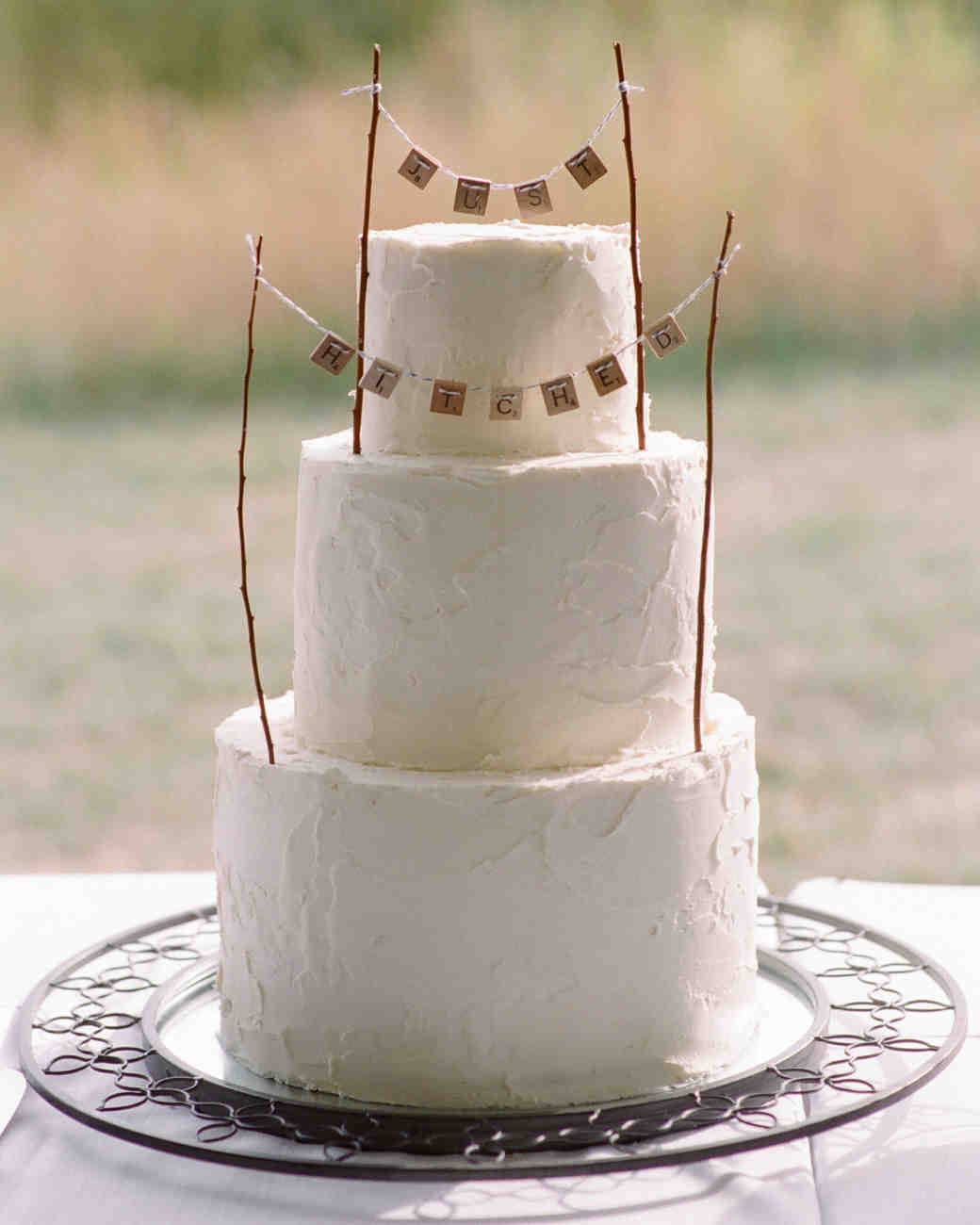 Three-Tiered White Wedding Cake with Scrabble Tile and Twine Garland Topper