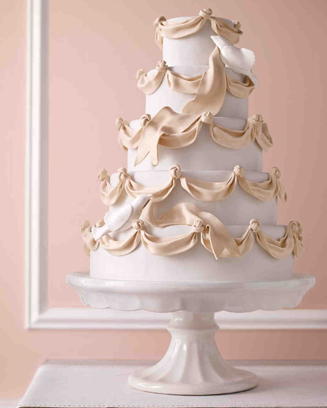 Five-Tiered White Wedding Cake with Cream-Colored Ribbon and Edible Doves
