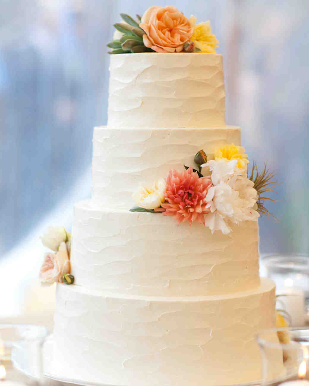 Four-Tiered White Wedding Cake with Orange, White, and Yellow Flowers