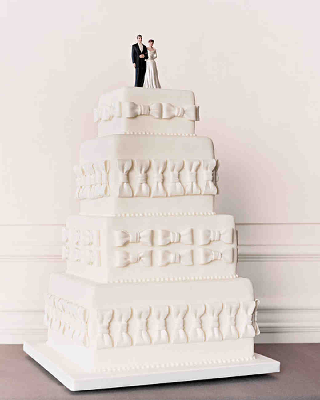 Four-Tiered White Wedding Cake with Traditional Topper and Bow Tie Design