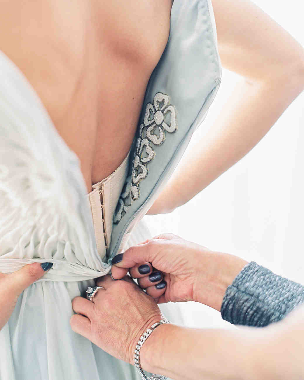 wedding dress being zipped