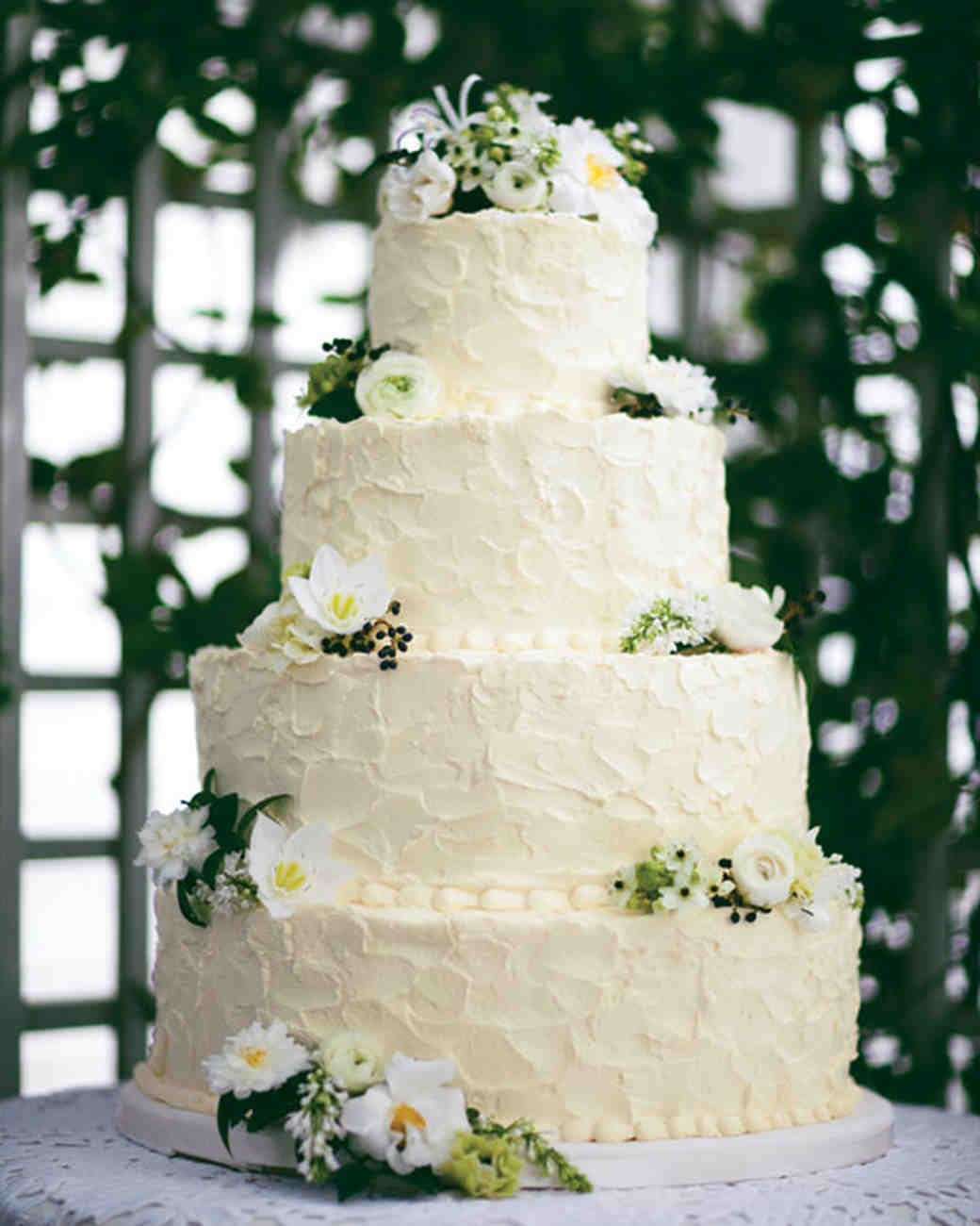 Four-Tiered White Wedding Cake with Green, Yellow, and White Flowers