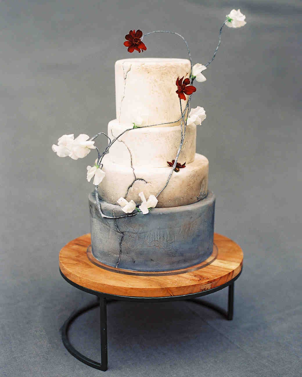 four tiered natural textured wedding cake with white and red floral accents