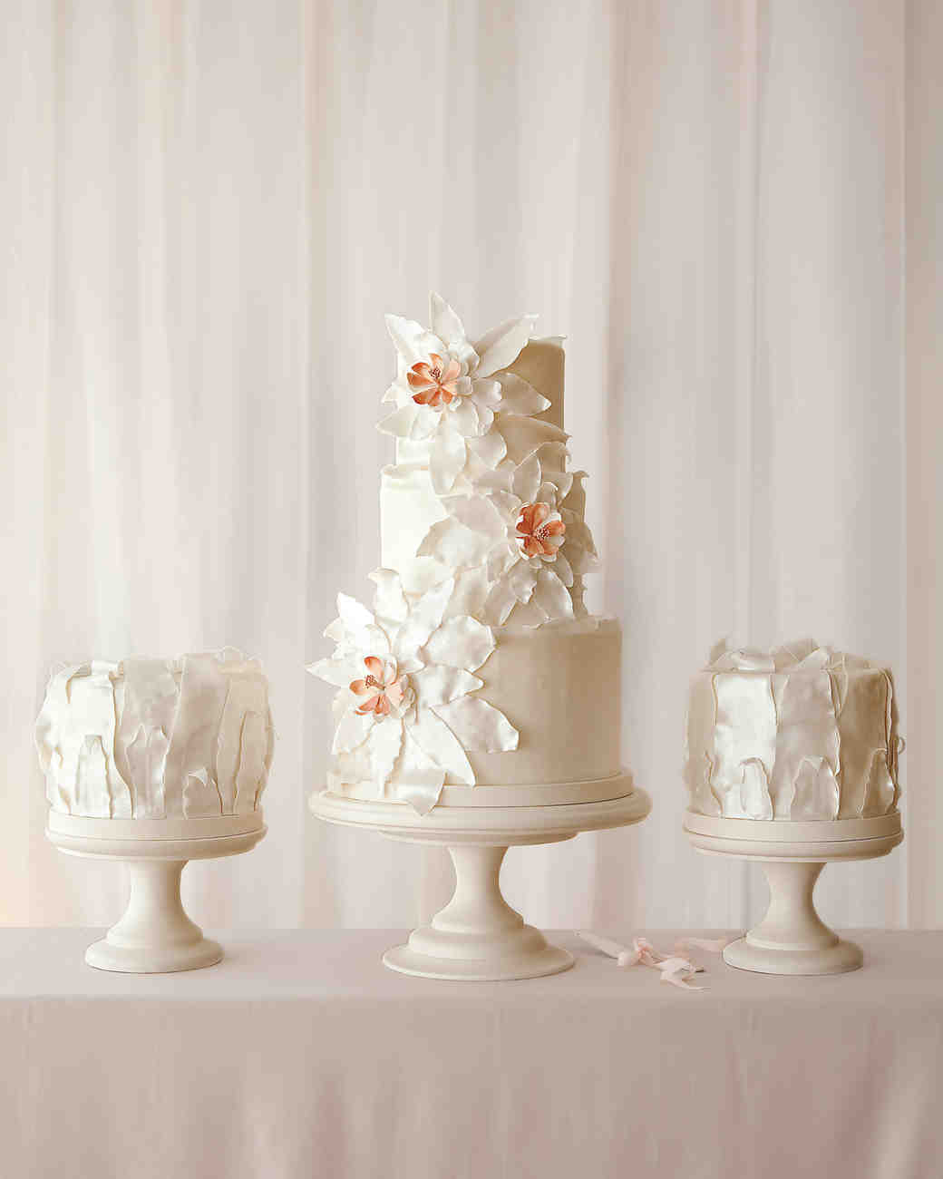Three White Wedding Cakes with Large Flowers