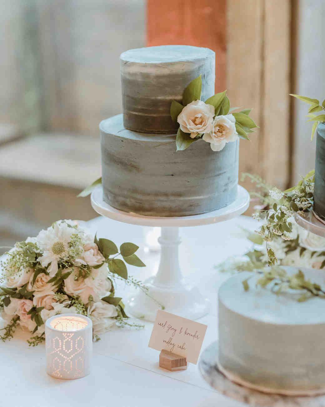 lavender and gray frosted two tiered wedding cake with floral accent