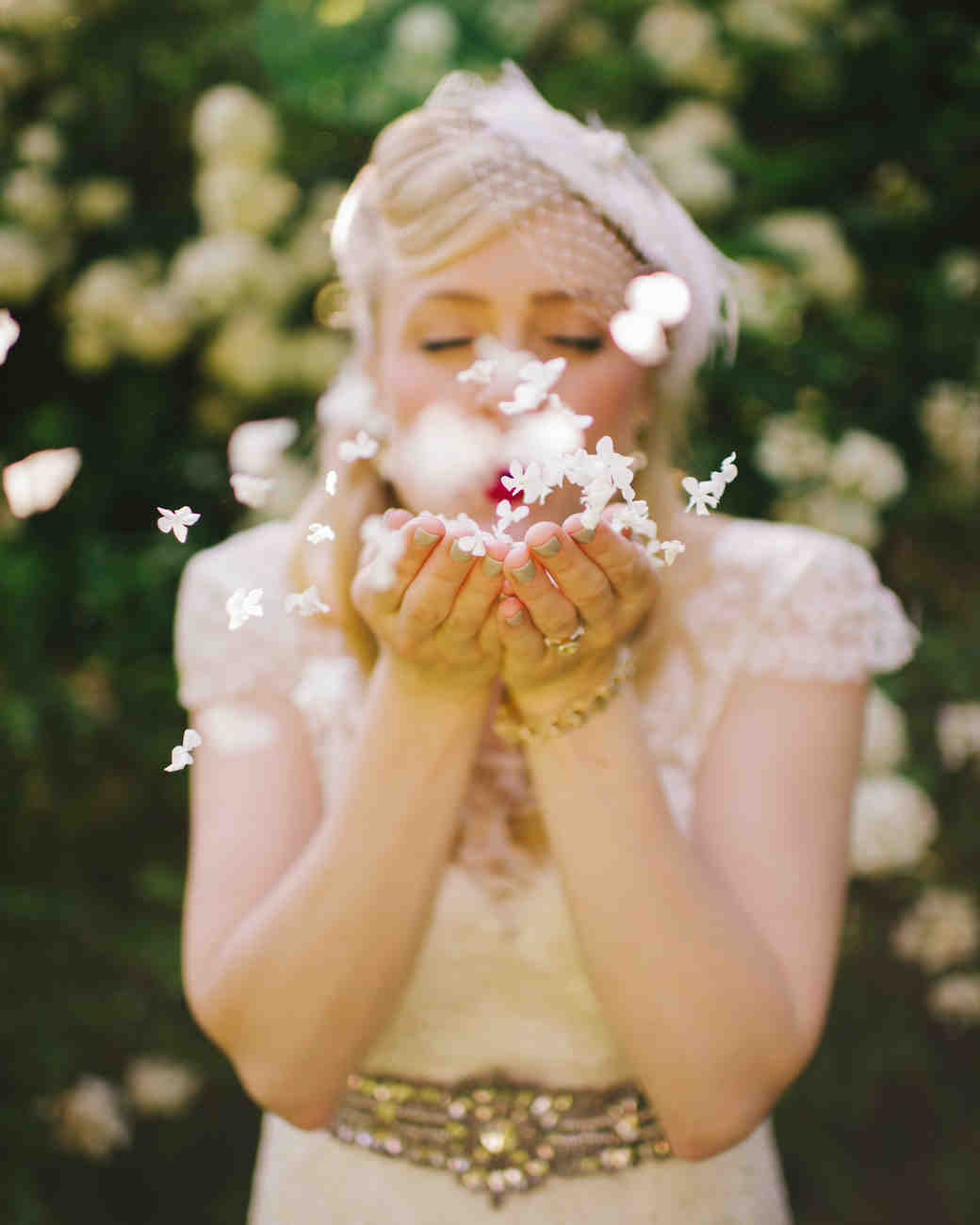 Bride Blowing White Petals Out of Hands