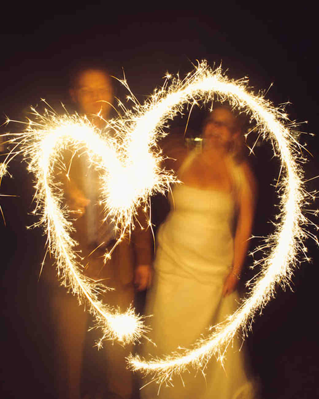 couple making heart with sparkler