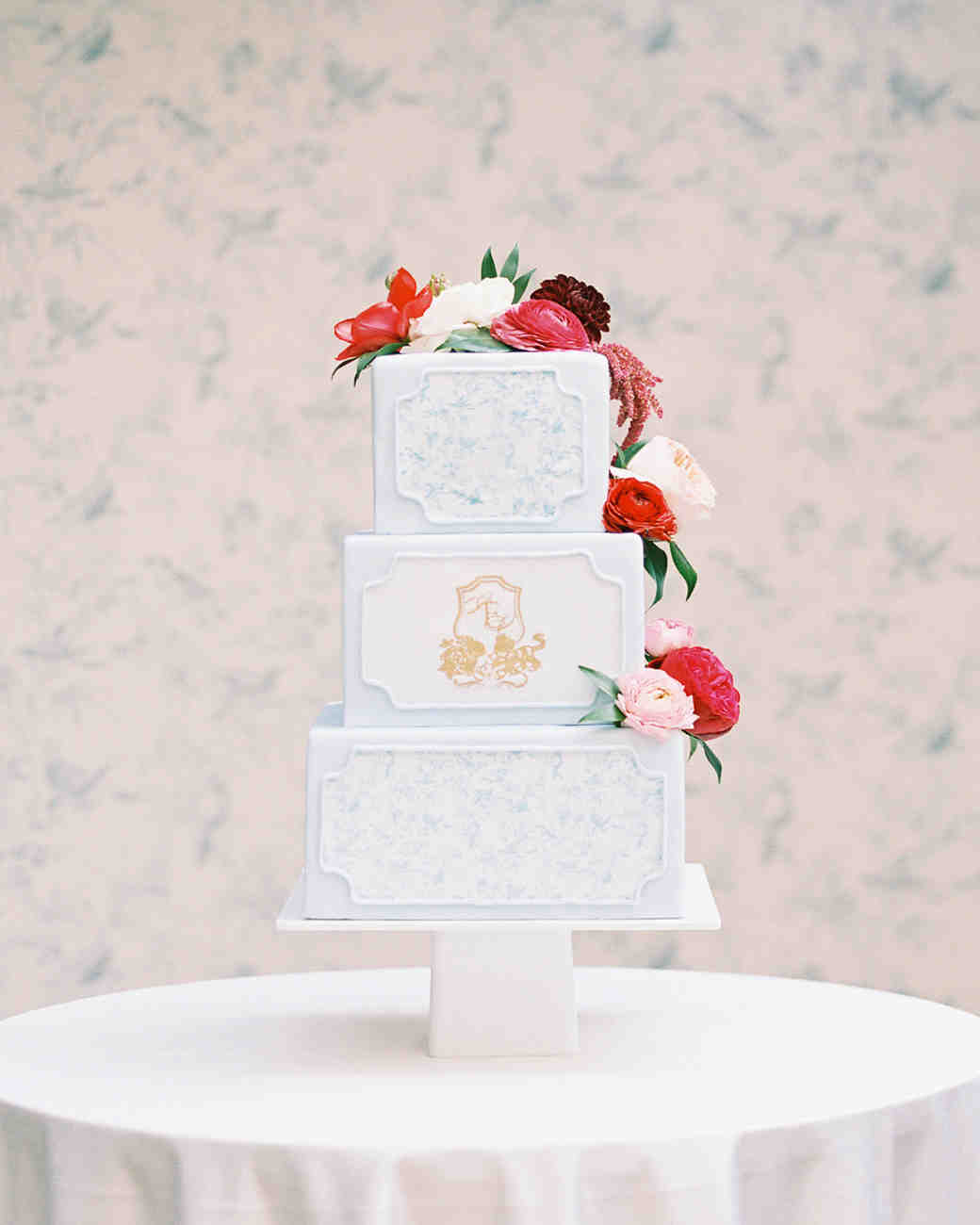 three tiered white wedding cake with floral topper