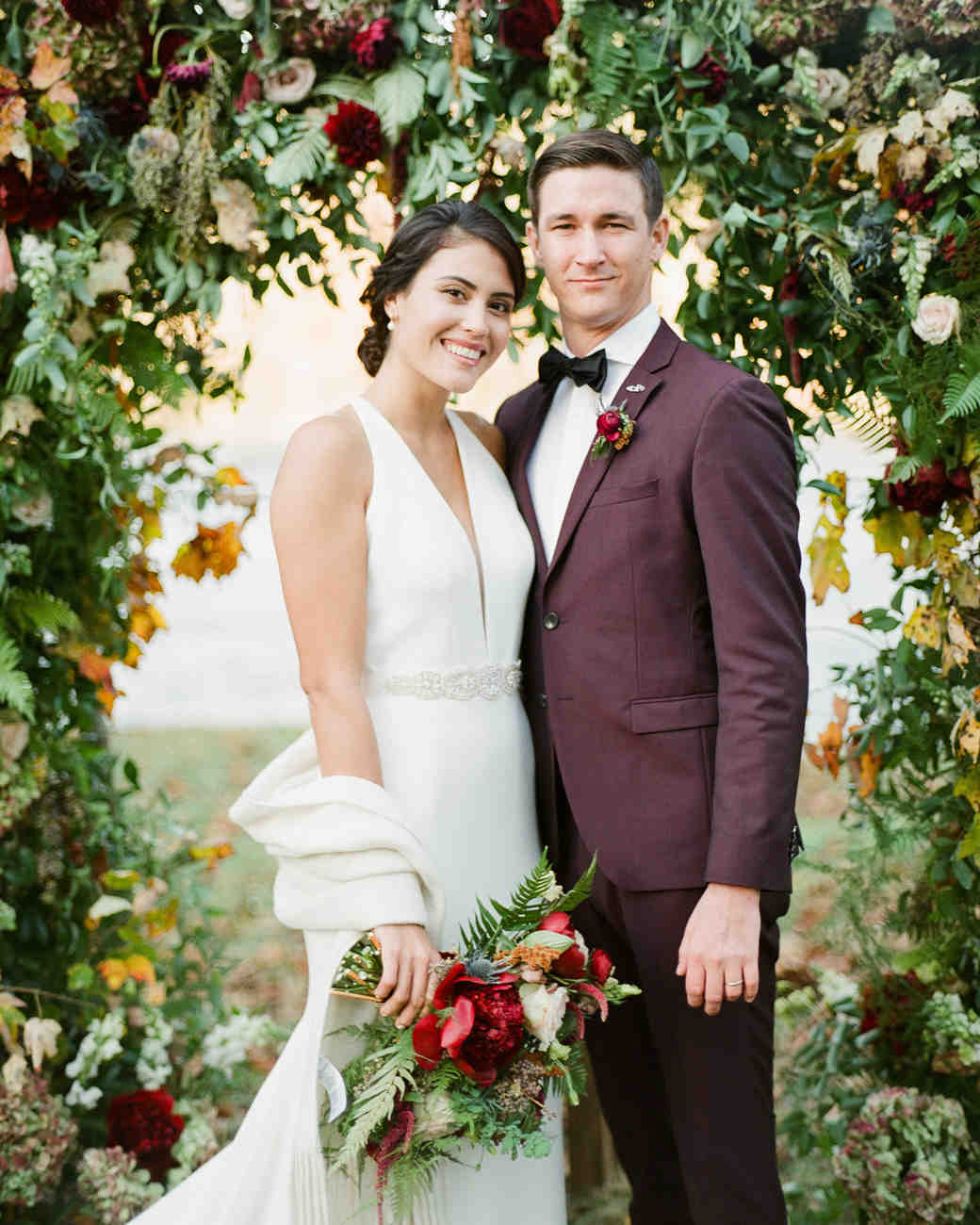 bride and groom standing under floral arch