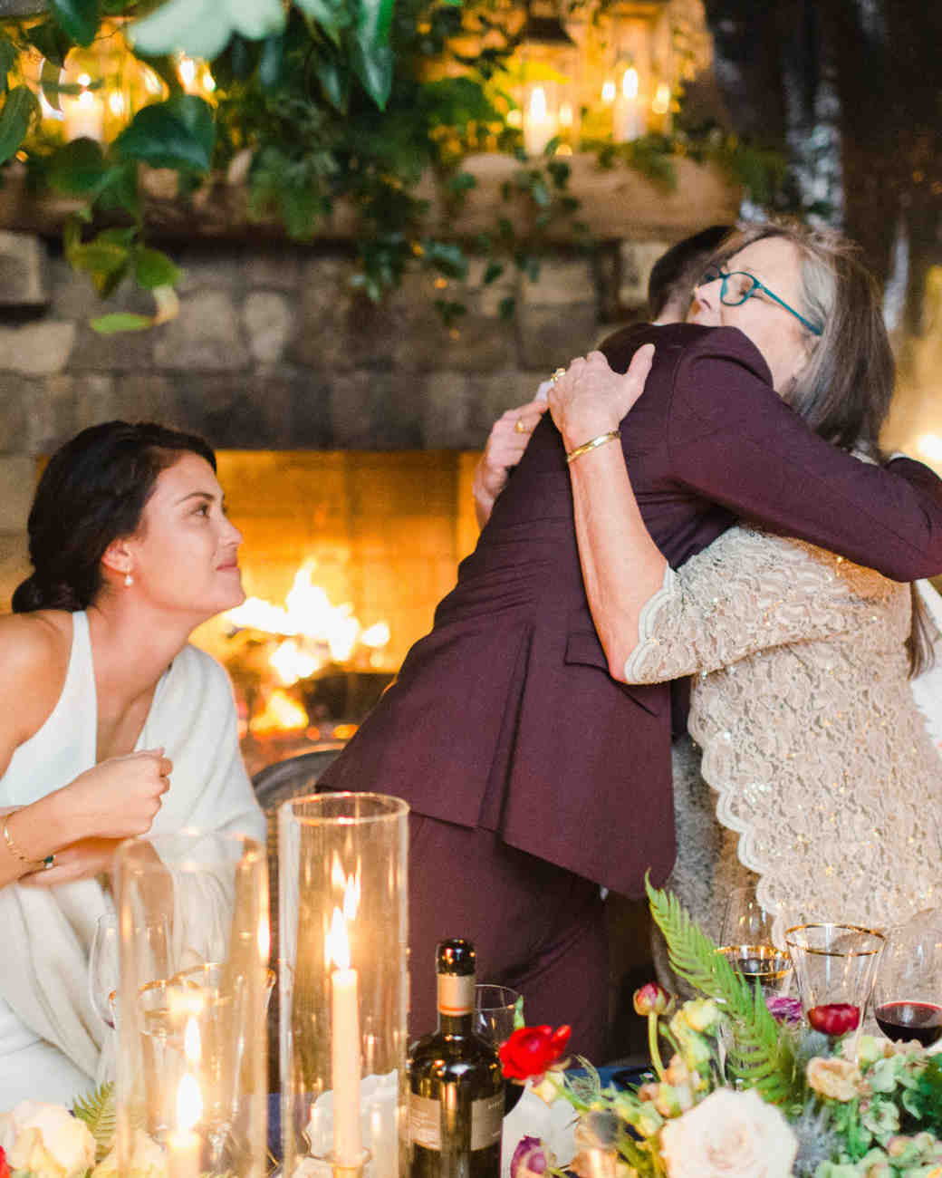mother of the groom hugging groom at reception table
