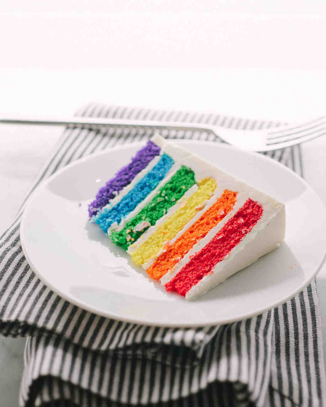 White Wedding Cake Slice with Rainbow Layers