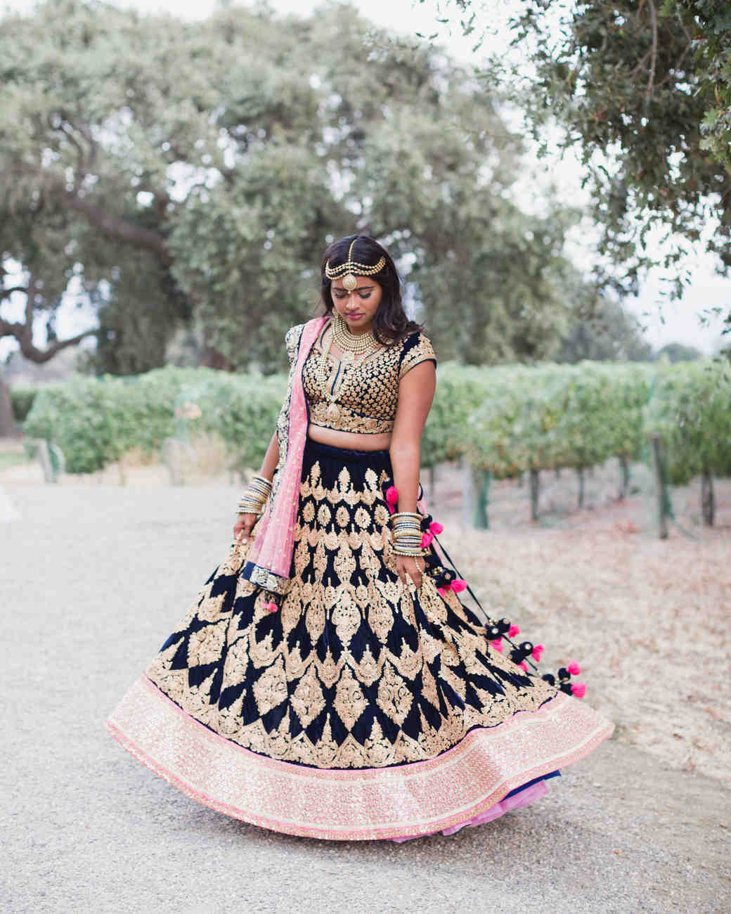 bride in black pink and gold indian lengha