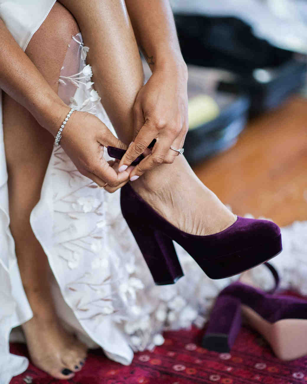 bride putting on aubergine velvet pumps