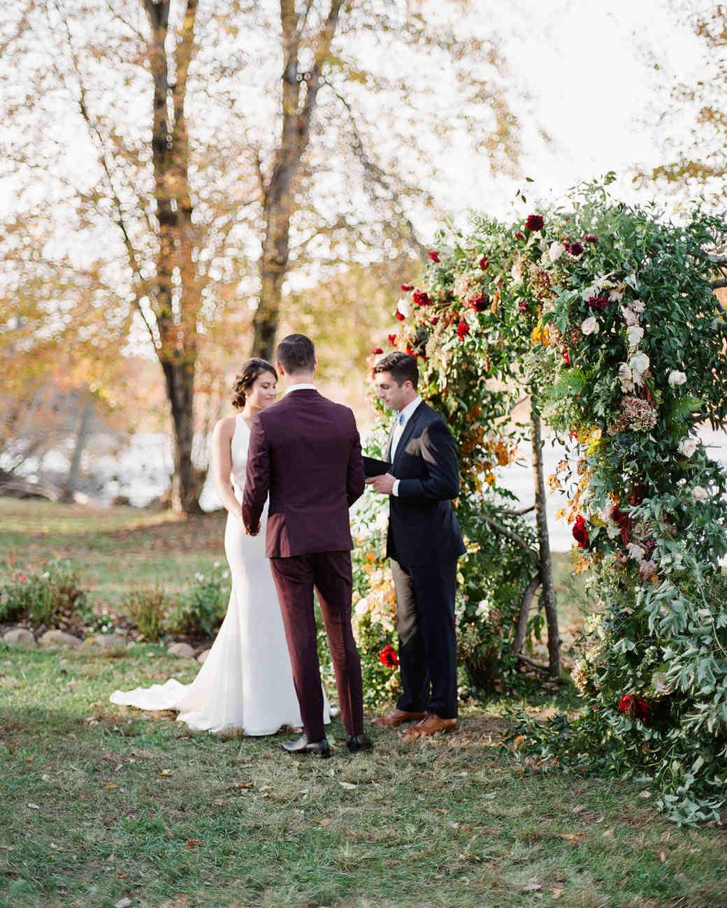 floral arch wedding ceremony backdrop by bride and groom