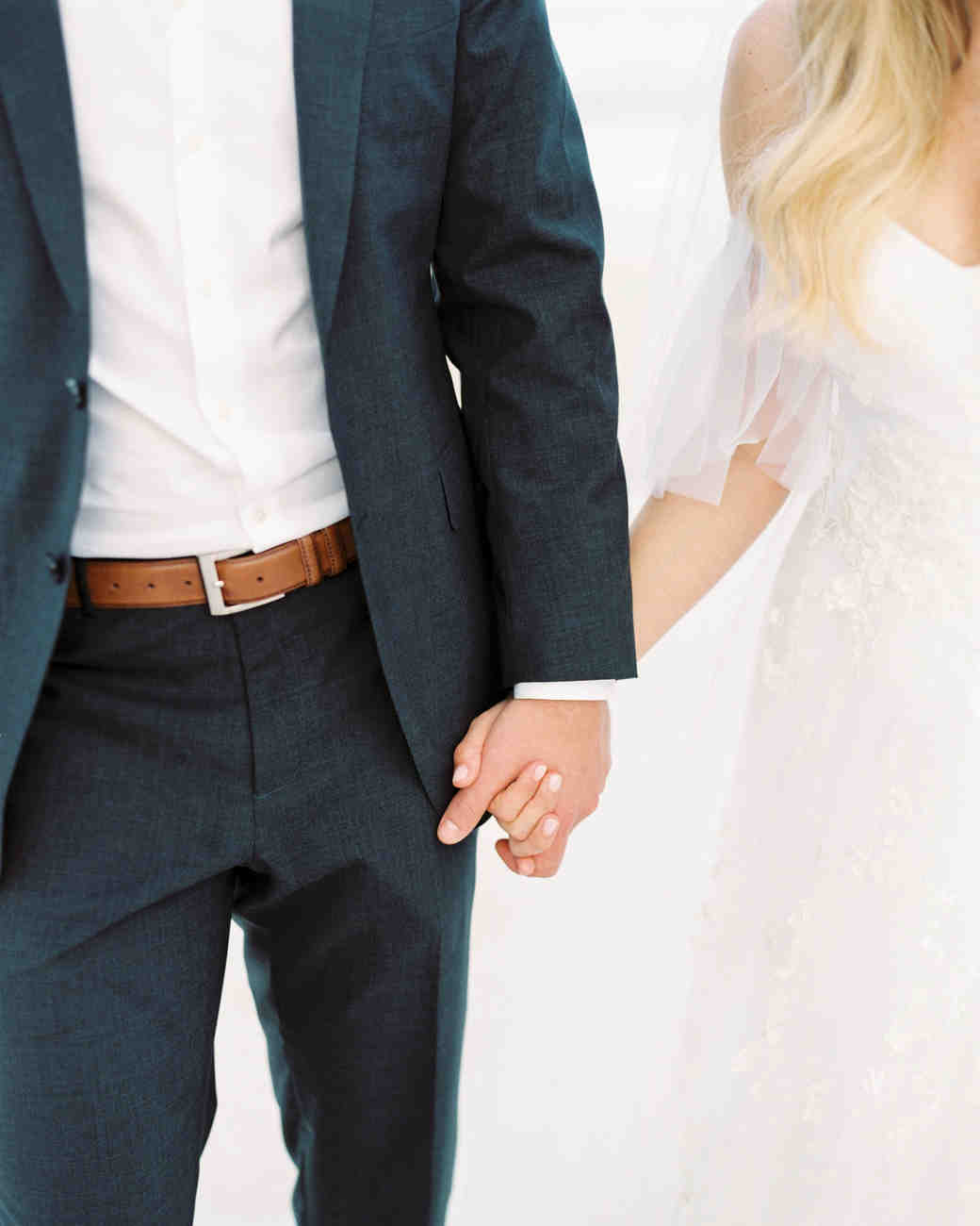 close-up of wedding couple holding hands