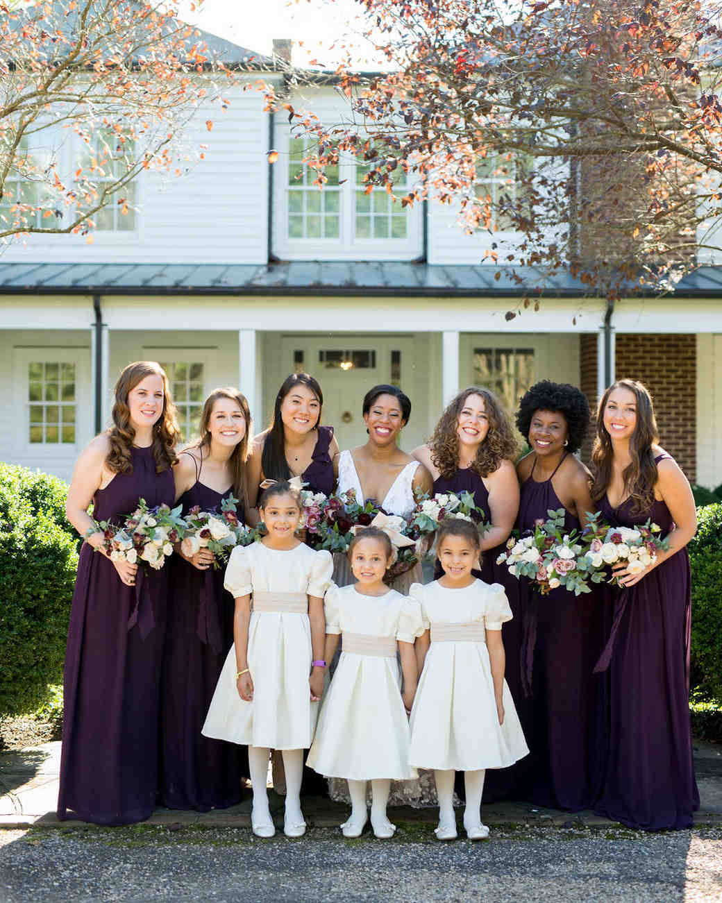 bridesmaids in aubergine dresses and flower girls in cream colored dresses