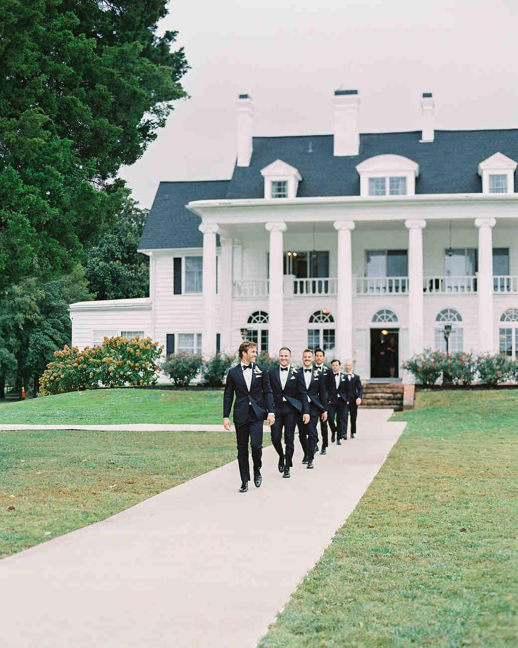 lauren alex wedding groomsmen walking in front of manor
