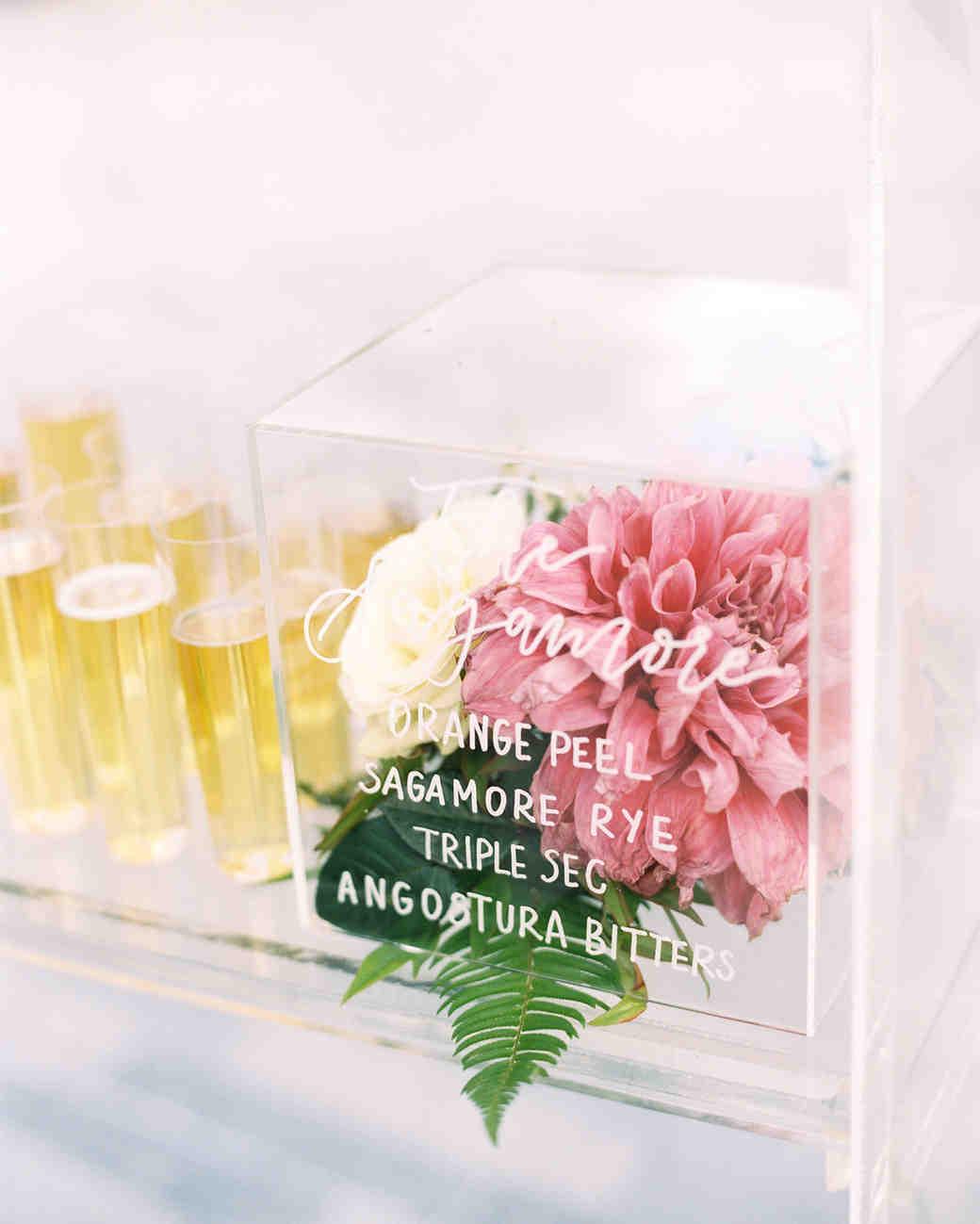 lucite cocktail menu box containing dahlias and roses