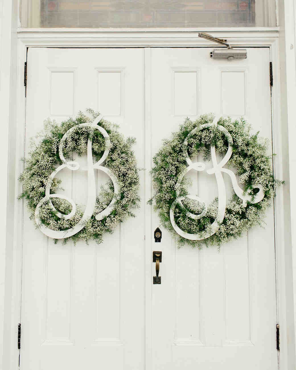 wedding wreaths monogramed hanging on white double doors