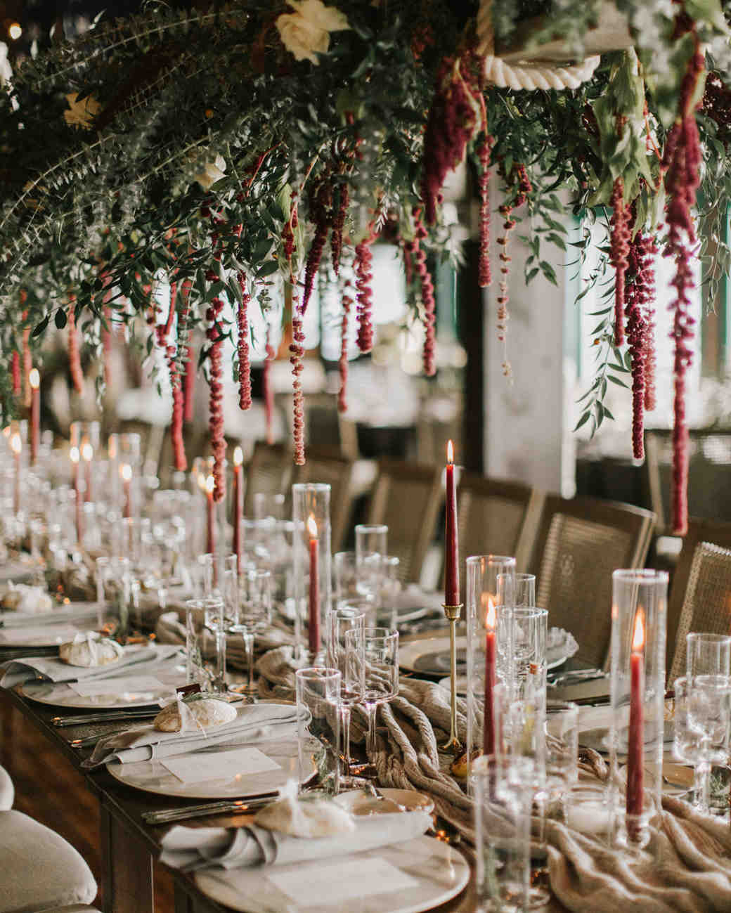 long wooden tables with gray runners, red taper candles in glass holders and hanging greenery