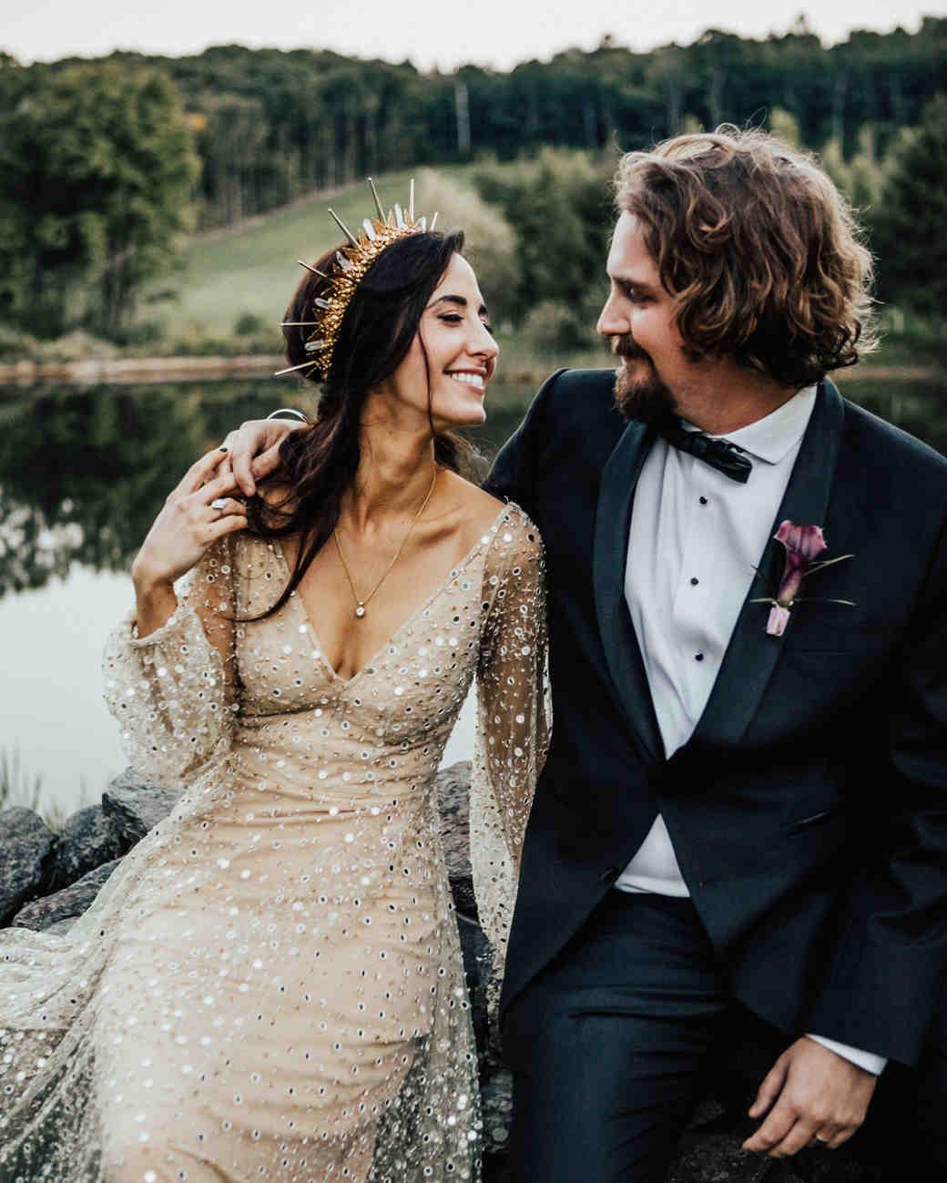 bride smiles at groom next to lake shore