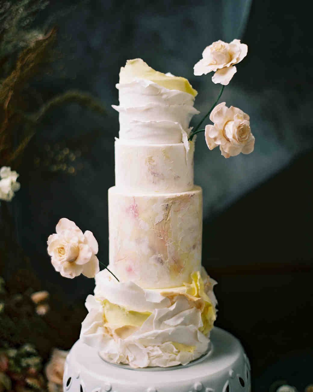 four-tiered cake with sugar flowers and buttercream