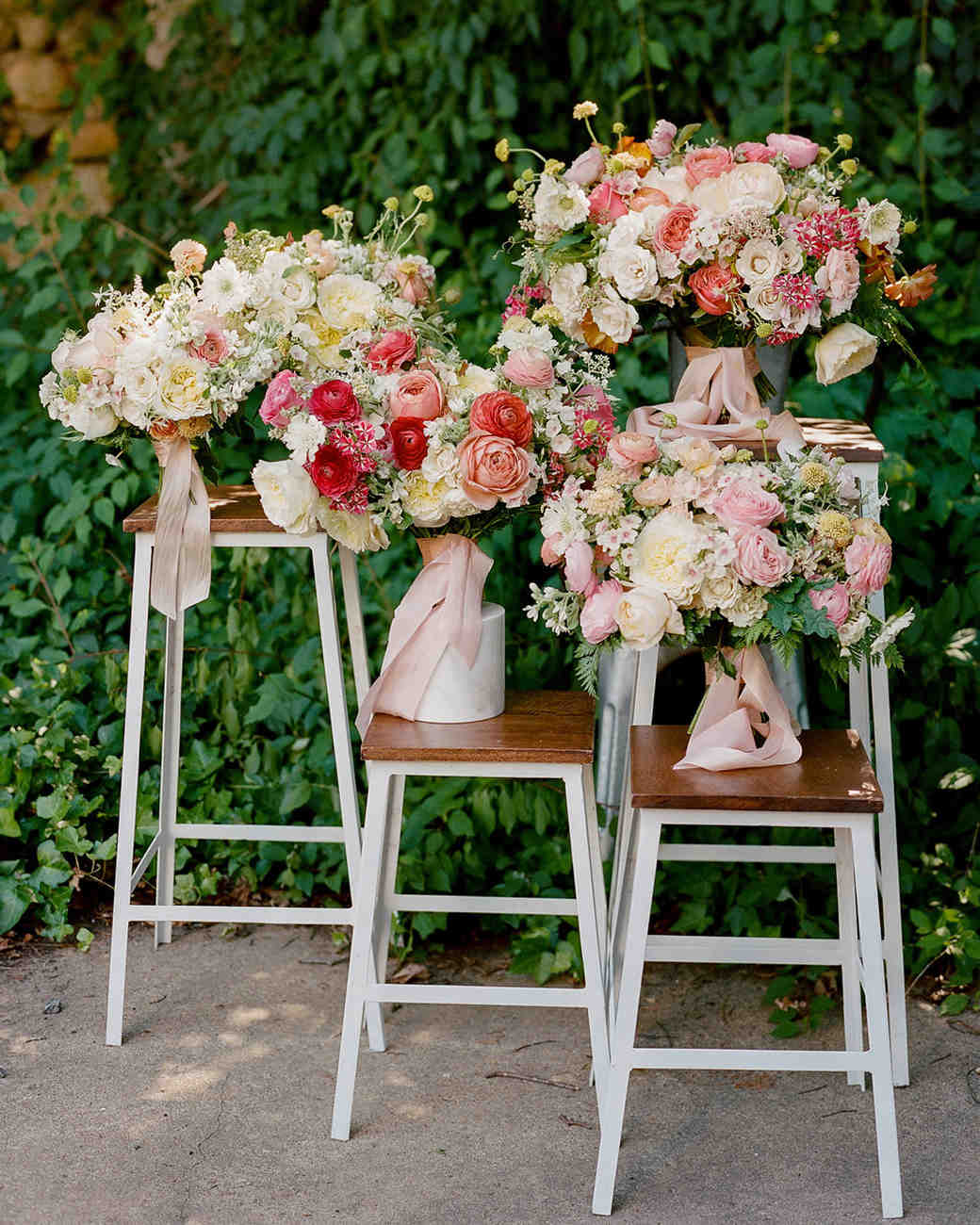 various bouquets of roses displayed on stools in front of wall of greenery