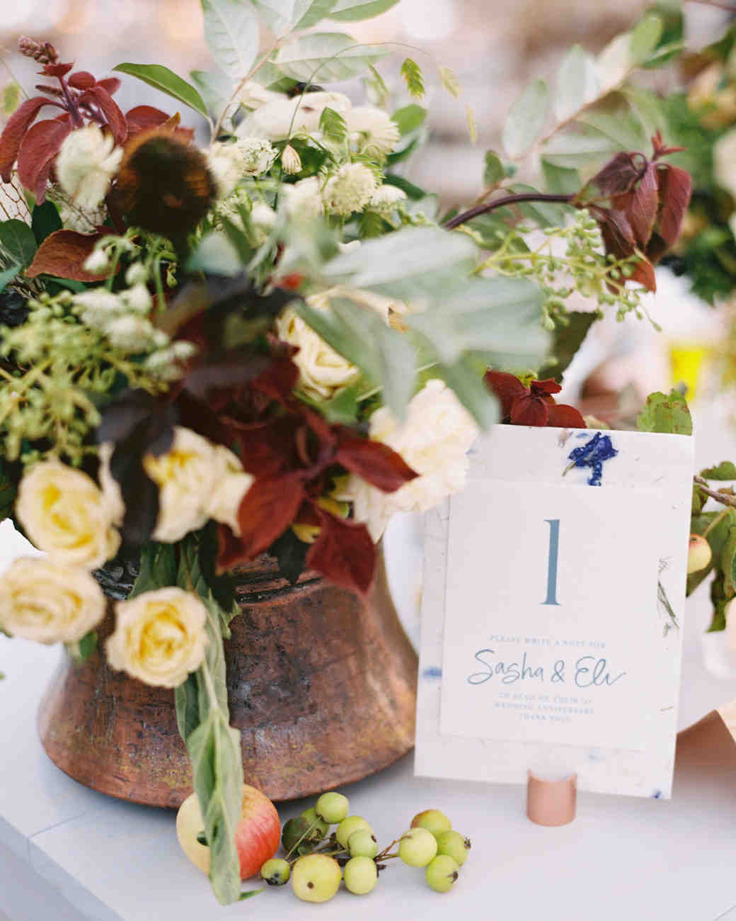 wedding reception table numbers next to floral arrangement
