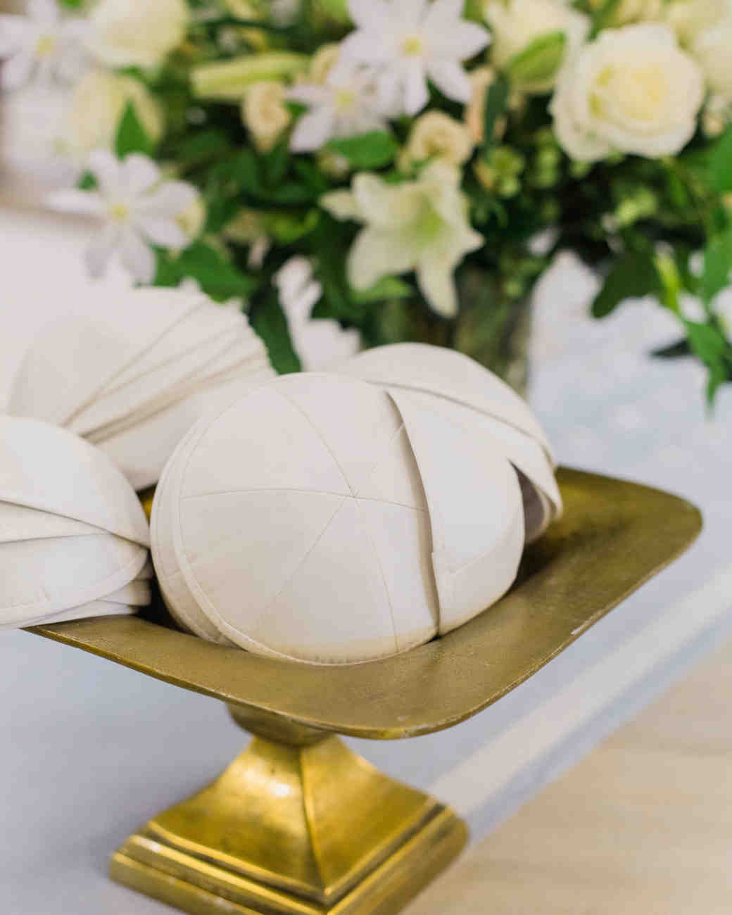 all-white yarmulkes on gold stand next to flowers