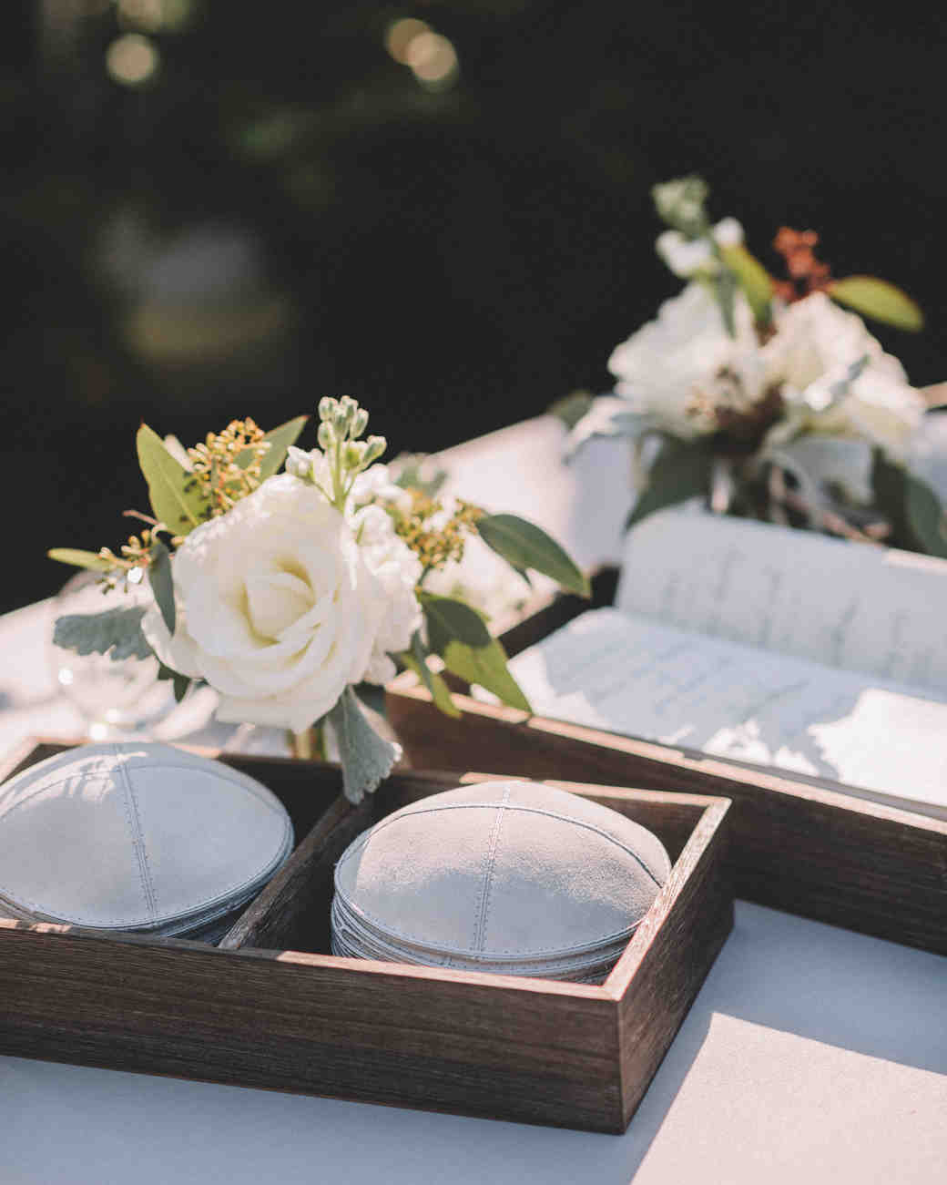 gray yarmulkes in wood box organizer on table with white flowers
