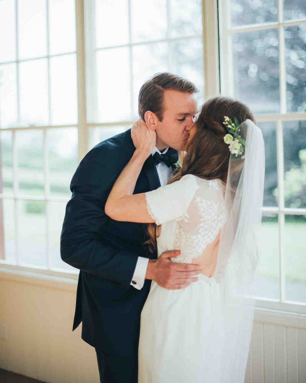 bride groom kiss in front of windows