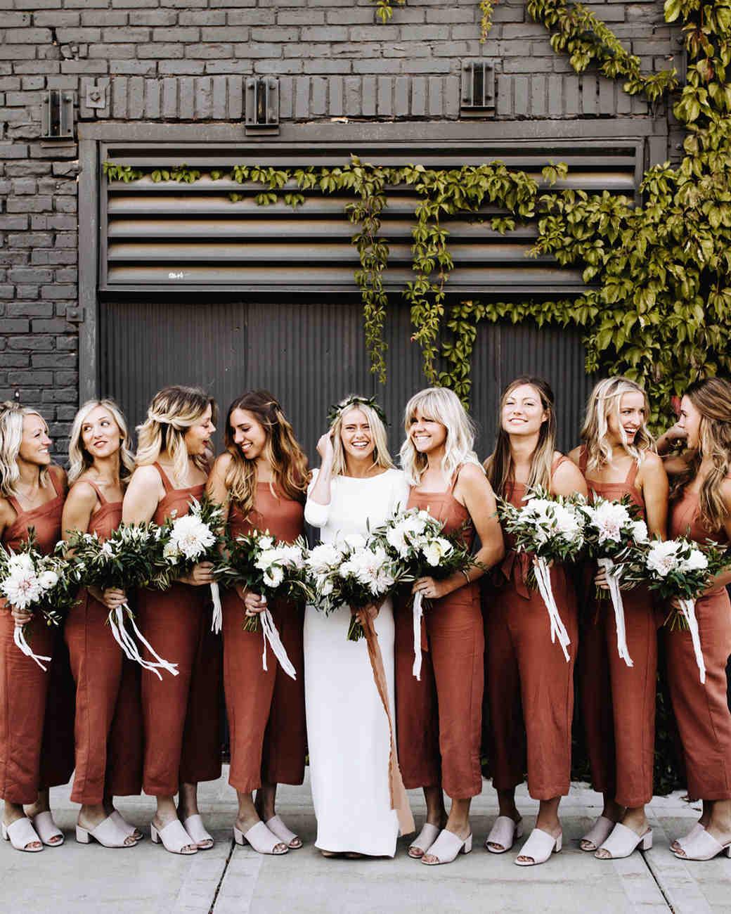 women standing in front of black brick wearing bridesmaids jumpsuits