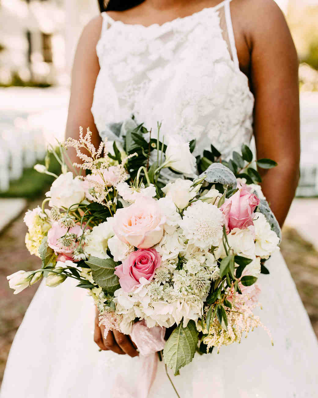 bride holding bouquet of roses and hydrangeas