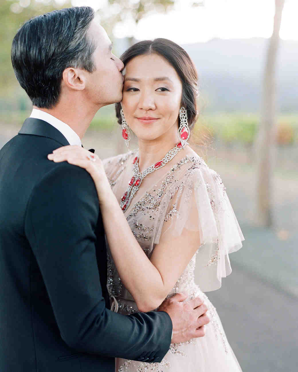 groom kisses bride on the forehead while standing for portraits