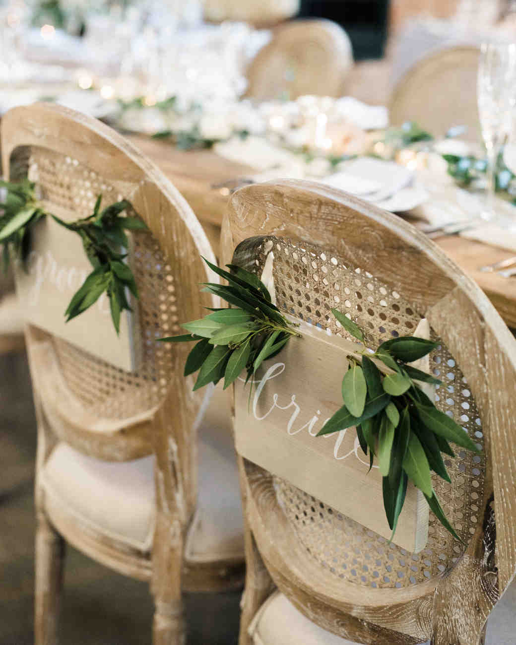 head table woven chairs hanging sign greenery